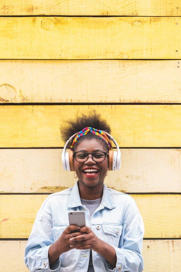 使用手机户外的美国黑人的十几岁的女孩 图库摄影
