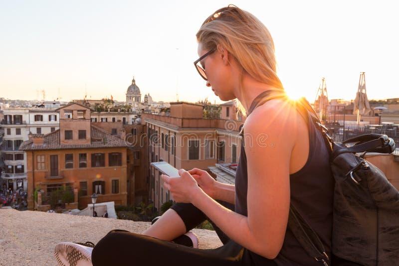 使用手机接近Piazza di Spagna,与西班牙步的地标正方形的女性游人旅行应用程序在罗马 免版税库存图片