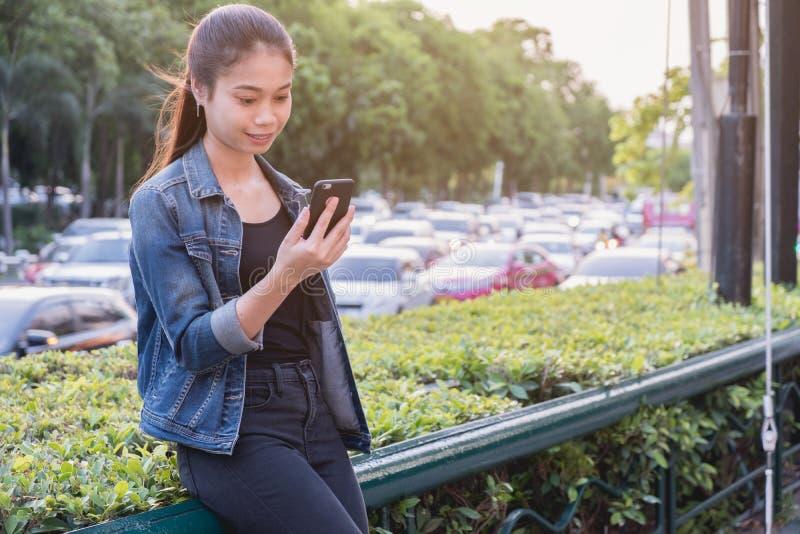 使用手机有堵车背景,关闭的妇女 免版税库存照片