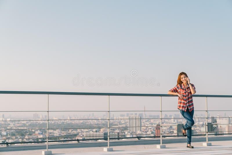 使用手机电话的美丽的亚裔妇女或大学生在屋顶单独或孤独,街市都市风景背景 免版税库存照片