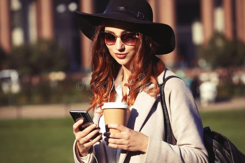 使用手机的一名相当微笑的妇女的画象,当拿着在城市街道上时的咖啡杯 免版税库存照片