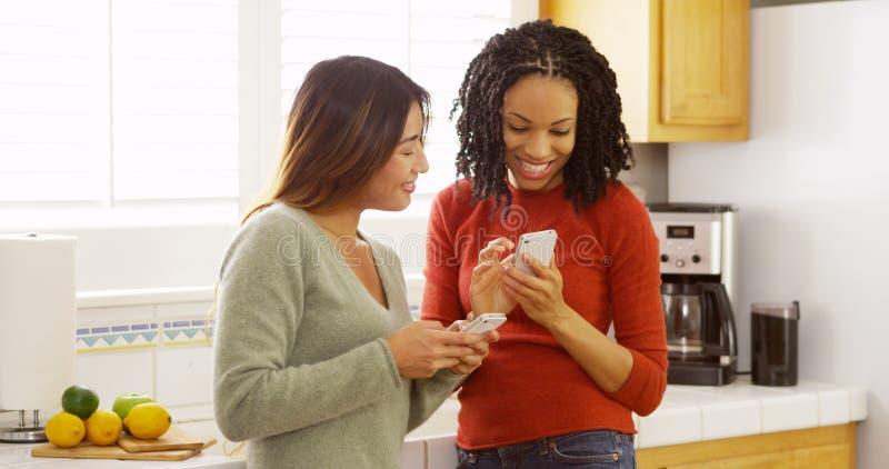 使用手机的两个亲密的朋友和倾斜反对厨台 免版税库存照片