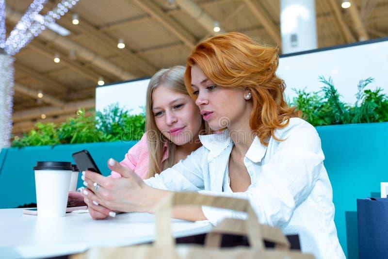 使用手机的两个愉快的女性朋友在咖啡馆在购物中心 免版税库存照片