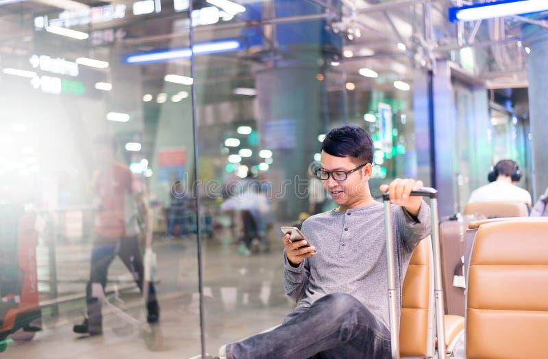 使用手机的亚裔人旅客在机场,使用手机连接概念的生活方式 库存图片