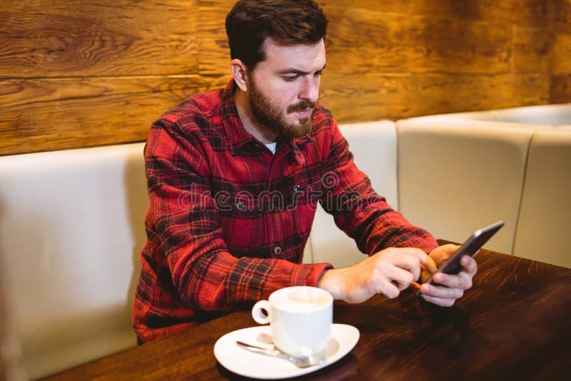 使用手机的人在桌在餐馆 图库摄影