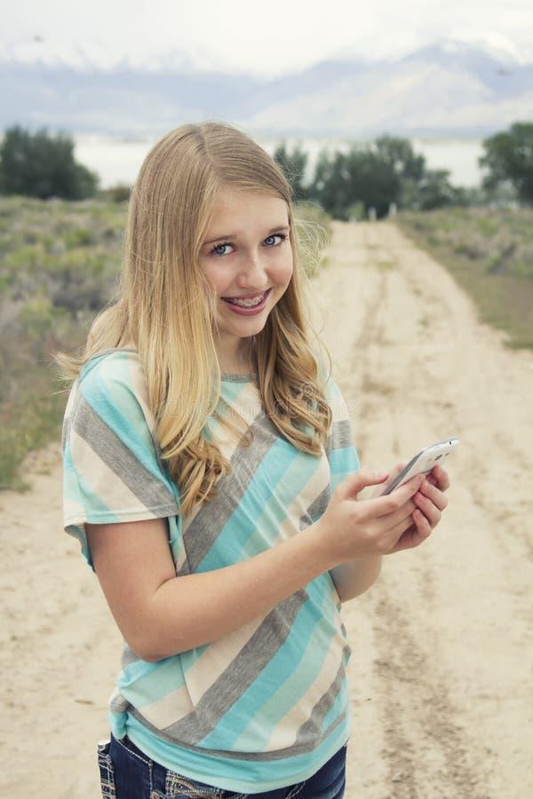 使用手机的十几岁的女孩步行沿着向下国家土路 免版税库存照片