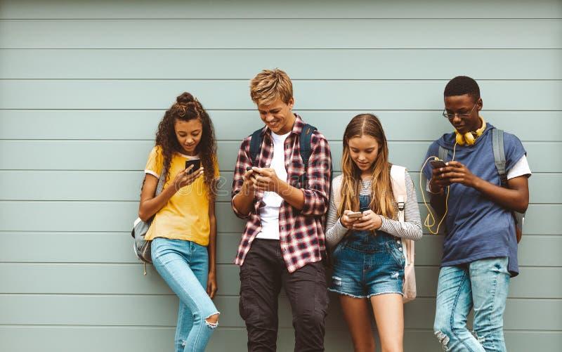 使用手机的十几岁的男孩和女孩站立户外 库存照片