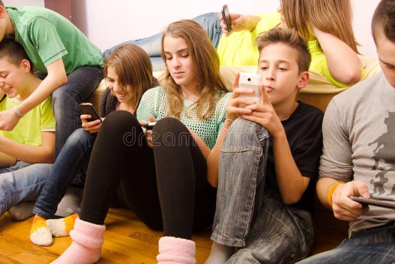 使用手机的十几岁的男孩和女孩,当在家时坐 免版税库存图片