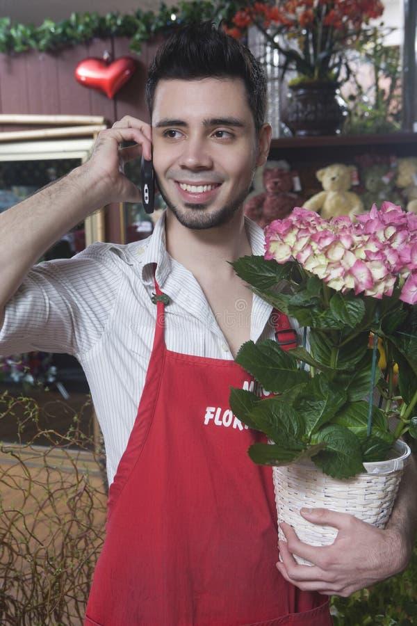 使用手机的卖花人,当拿着八仙花属时 免版税库存照片