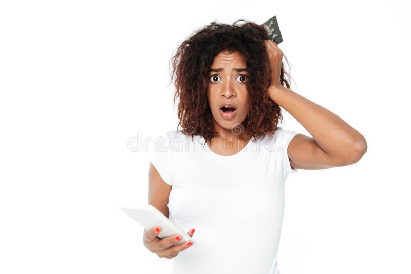 使用手机的哀伤的年轻非洲夫人拿着信用卡 图库摄影