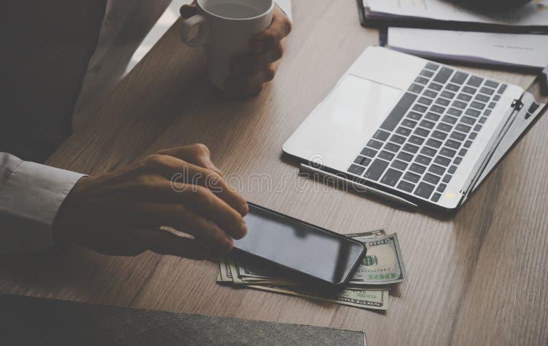 使用手机的商人兑现在办公室d的金钱 免版税库存照片