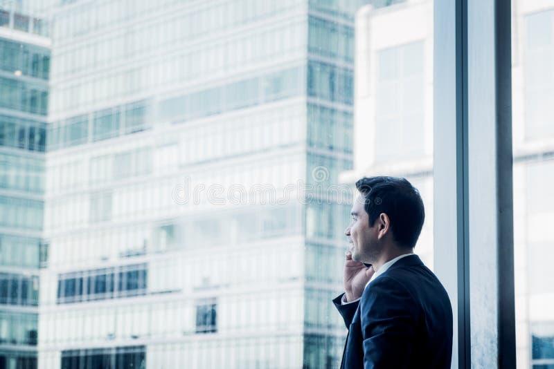 使用手机的商人在办公室buil的办公室窗口附近 免版税库存照片