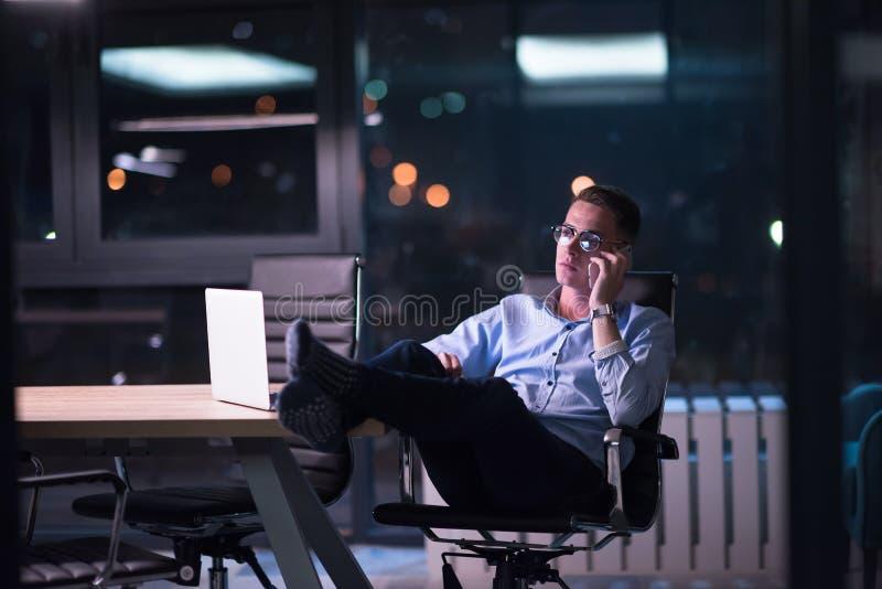 使用手机的商人在黑暗的办公室 图库摄影
