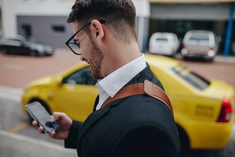 使用手机的商人,当走在街道上时 免版税库存照片