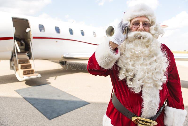 使用手机的圣诞老人反对私人喷气式飞机 图库摄影