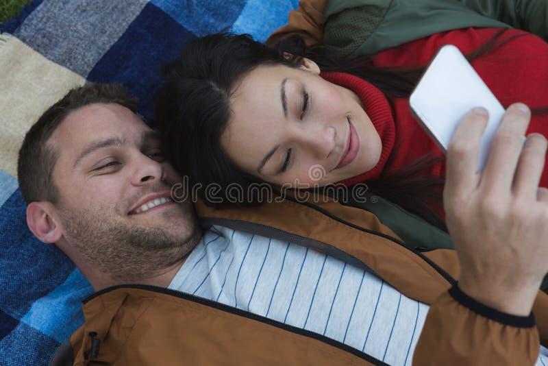 使用手机的夫妇,当说谎在野餐毯子时 库存图片