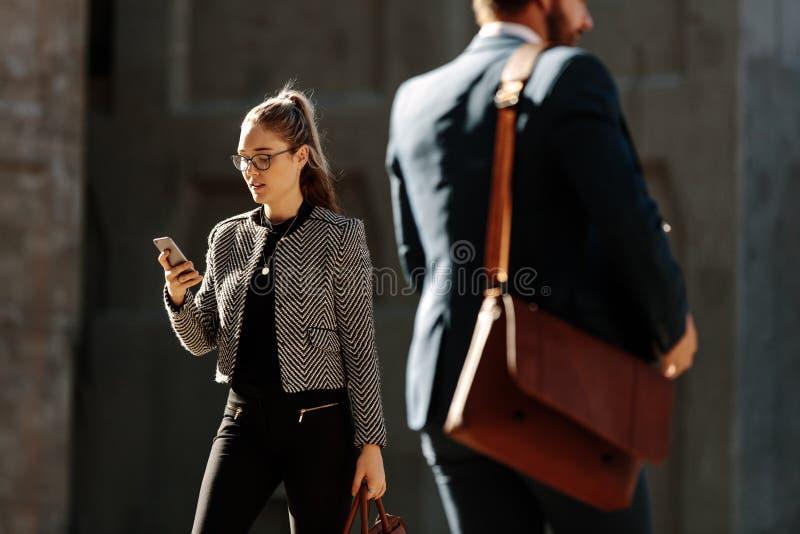使用手机的女实业家,当去办公室时 库存图片