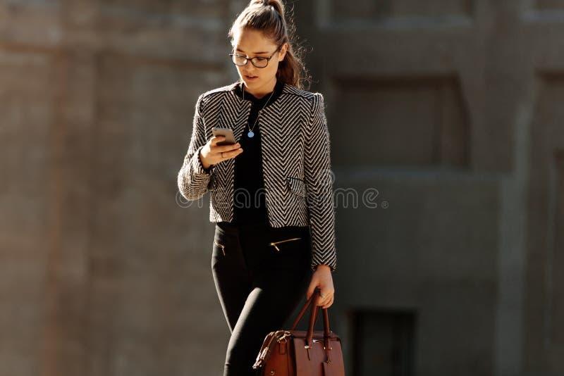 使用手机的女实业家,当通勤对办公室时 库存图片