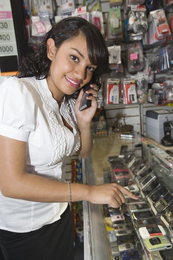 使用手机的女性所有者在流动商店 免版税库存图片