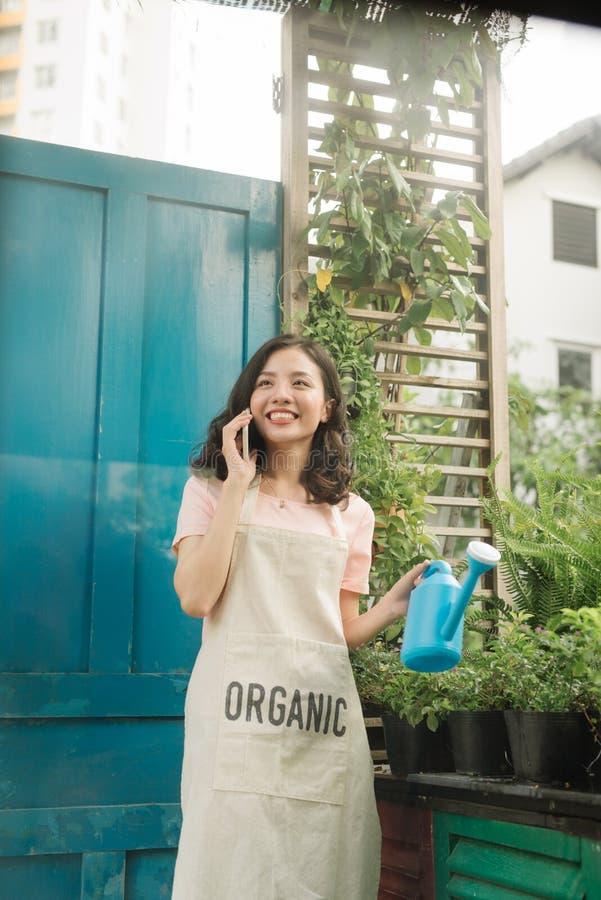 使用手机的女性花匠,当浇灌在她的庭院时 免版税库存照片