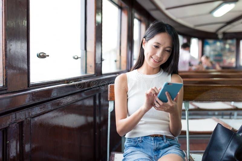 使用手机的妇女和乘轮渡在香港 免版税库存照片
