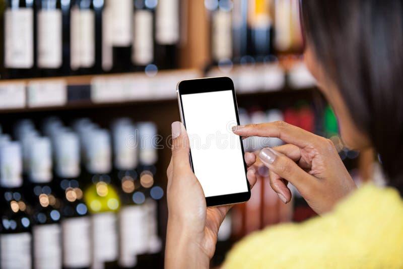 使用手机的妇女在杂货部分 库存照片