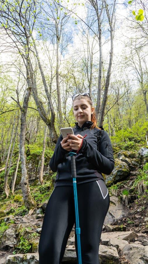 使用手机的妇女在走在森林里和使用她的现代手机,为照相的森林愉快的少女 库存照片