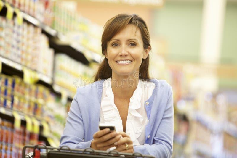 使用手机的妇女在超级市场 库存照片