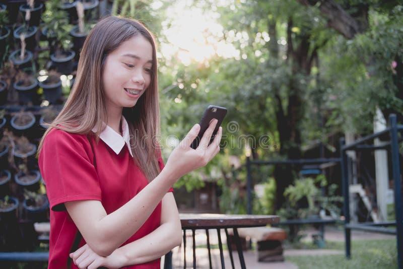 使用手机的妇女,当立场在公园时 库存照片