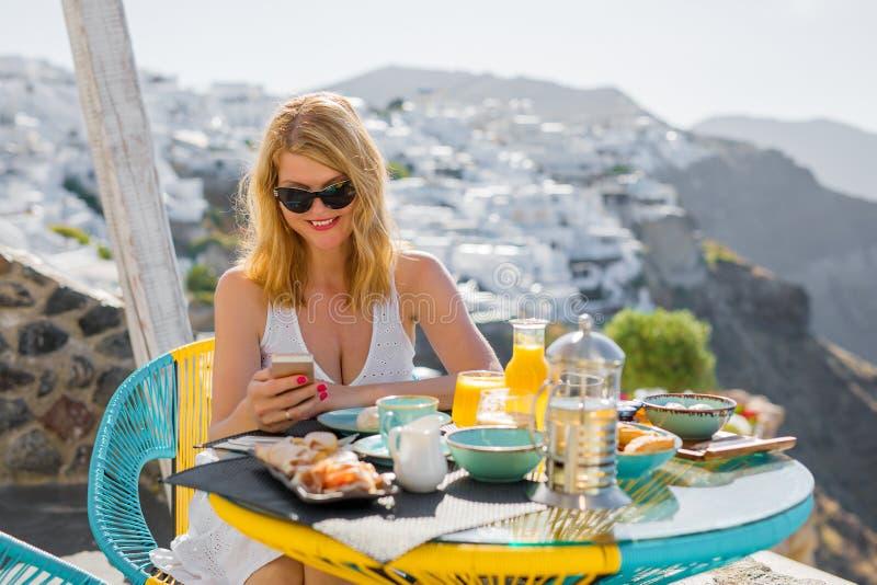 使用手机的妇女,当食用早餐在圣托里尼时 免版税库存图片