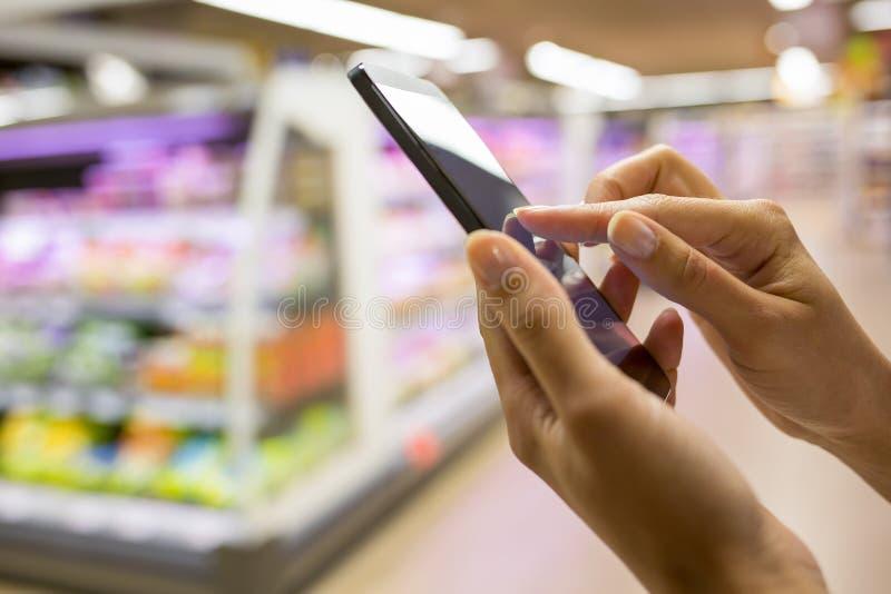 使用手机的妇女,当购物在超级市场时 免版税库存图片