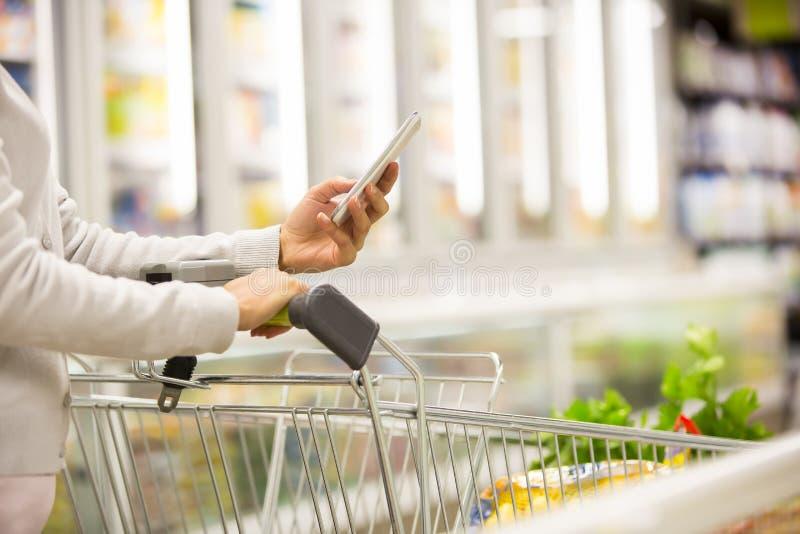 使用手机的妇女,当购物在超级市场时 免版税库存照片