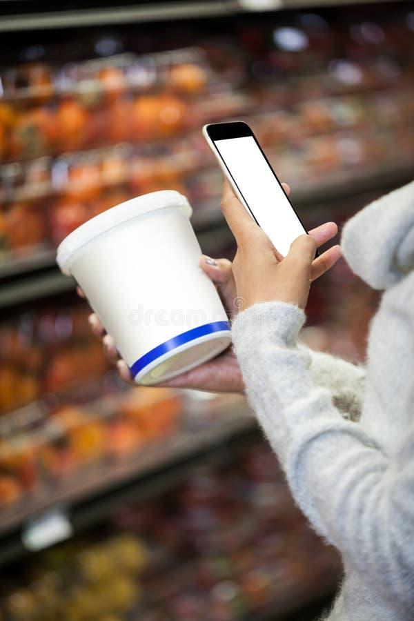 使用手机的妇女,当购物杂货时 免版税库存图片