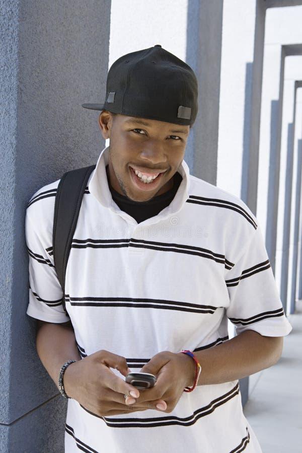 使用手机的学生在学院走廊 库存图片