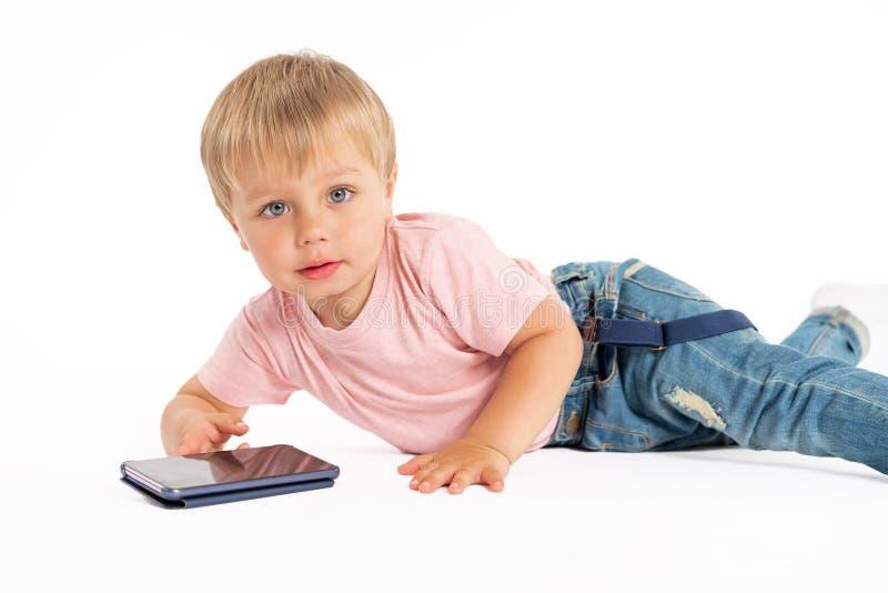 使用手机的小男孩 使用在智能手机的孩子 技术、流动应用程序、孩子和父母亲情况通知 免版税库存照片