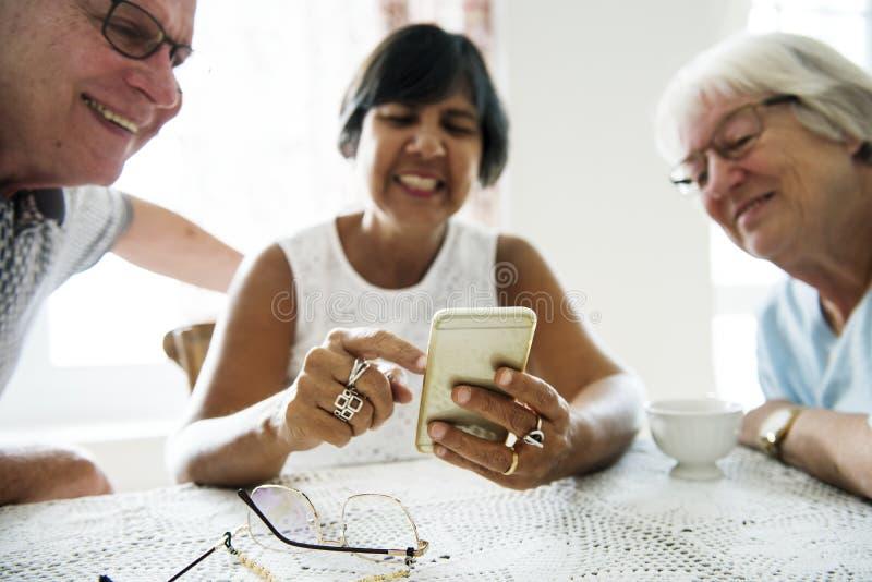 使用手机的小组不同的资深人民 免版税库存照片