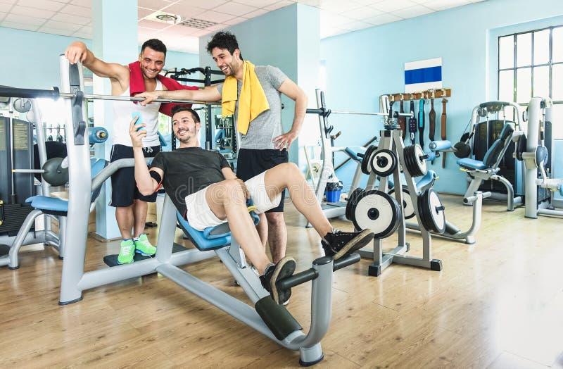 使用手机的小组嬉戏朋友在健身房健身俱乐部 免版税图库摄影