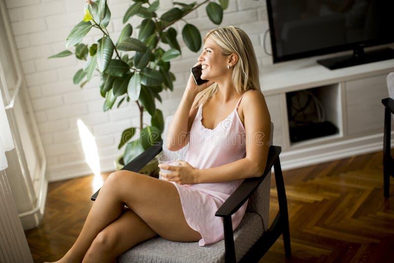 使用手机的少妇和拿着杯水在 免版税库存图片
