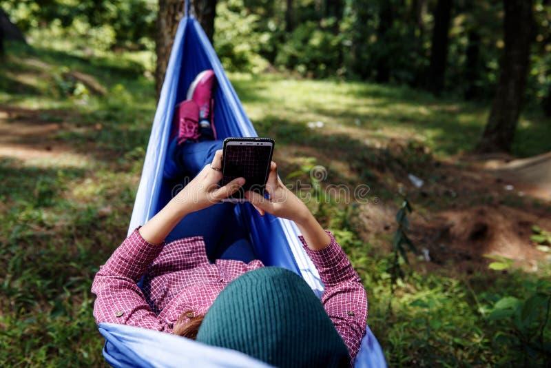 使用手机的年轻亚裔徒步旅行者妇女,当放松在火腿时 库存照片