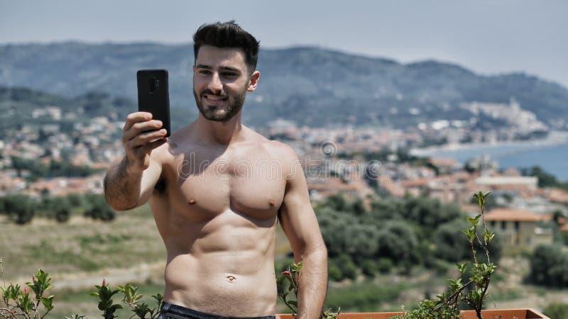 使用手机的年轻人采取selfie 库存图片