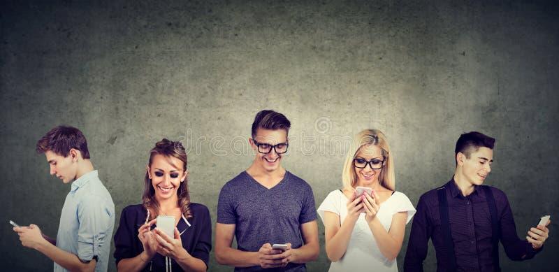 使用手机的年轻偶然人民一起站立对混凝土墙 免版税库存图片
