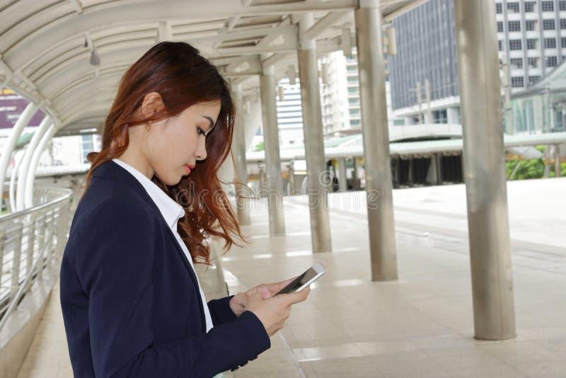 使用手机的年轻可爱的女商人广角射击在她的手在都市室外背景 免版税库存照片