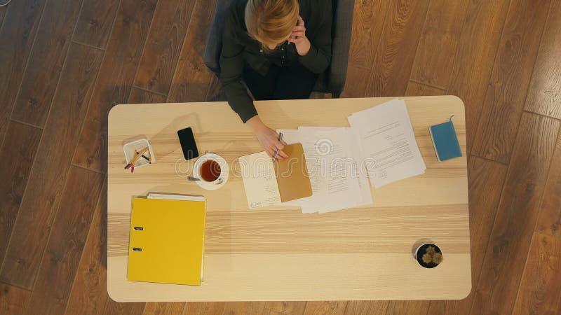 使用手机的年轻女性女实业家在书桌,有电话 免版税库存照片