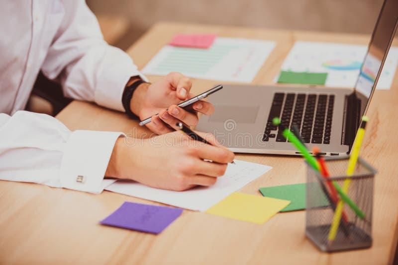 使用手机的年轻经理人在办公室和在纸贴纸做笔记 特写镜头手,桌,膝上型计算机 图库摄影