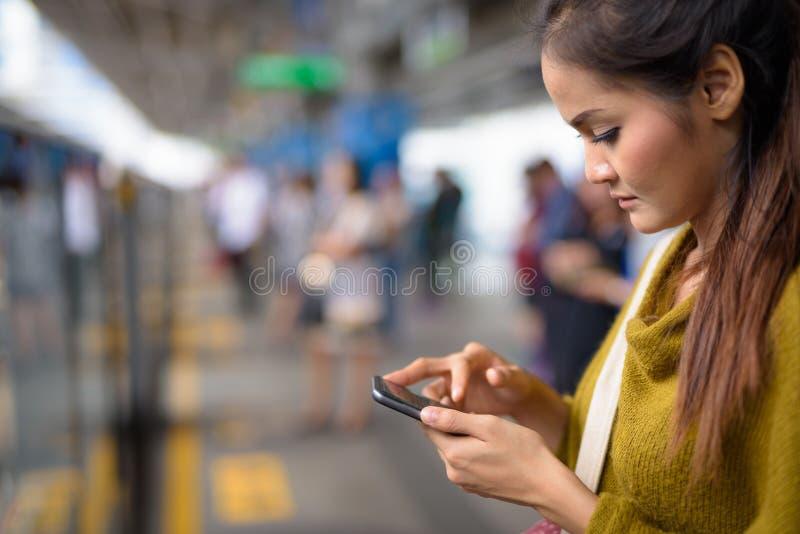 使用手机的年轻美丽的亚裔妇女在火车站 库存照片