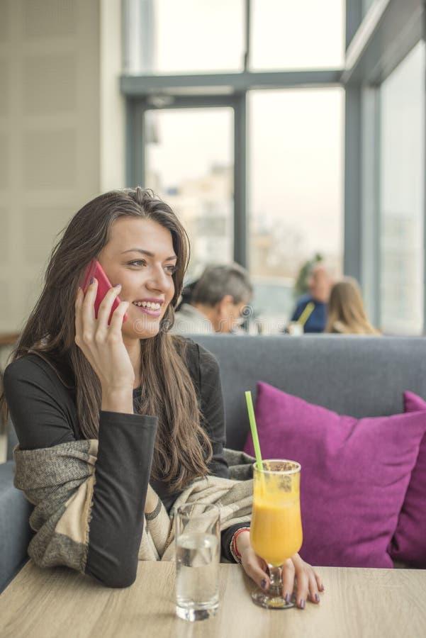 使用手机的年轻美丽的妇女画象在咖啡s 库存图片