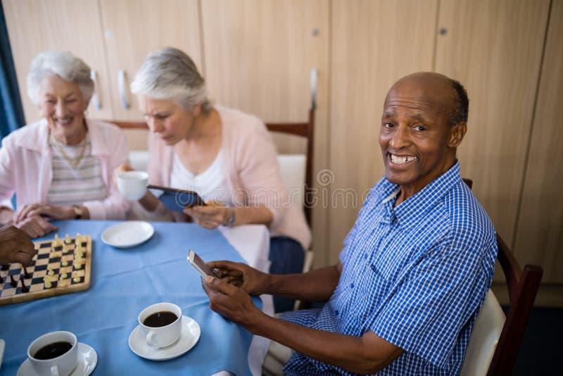 使用手机的微笑的老人,当食用与朋友时的茶 免版税库存图片