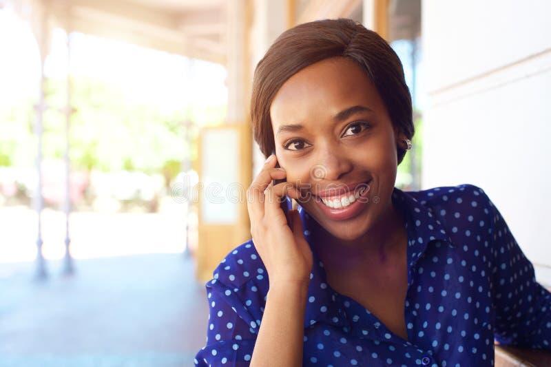 使用手机的微笑的非裔美国人的女商人 库存图片