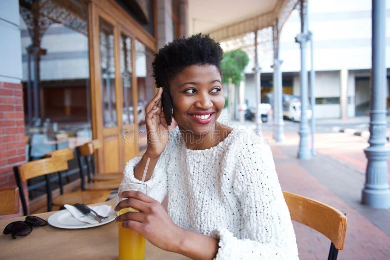 使用手机的微笑的非洲女孩在室外咖啡馆 免版税库存图片