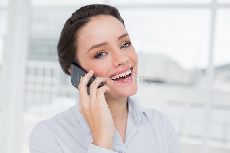 使用手机的快乐的典雅的年轻女实业家 库存照片